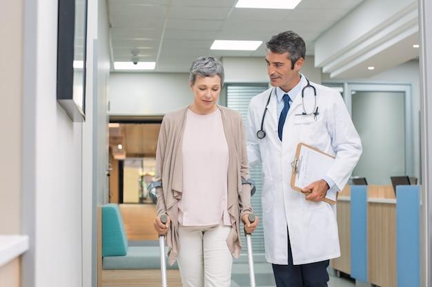 Врач и пациент с костылями