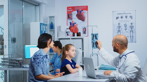 診療所に座ってx線を見ている医師と患者。医療サービスの相談、診療所の病院のキャビネットでのレントゲン治療を提供する医学の医師の専門家