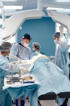 Врач и помощник хирурга отправляют ручной хирургический инструмент для спасения пациента в операционной в больнице, неотложной помощи, хирургии, медицинских технологий, рака здравоохранения, концепции болезни.