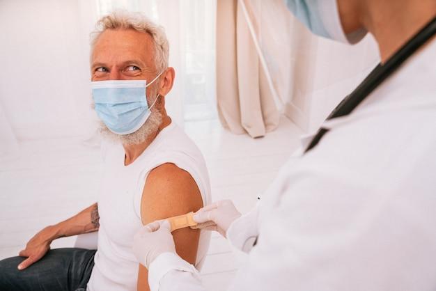 의사는 코 비드 백신 후 환자에게 패치를 적용합니다