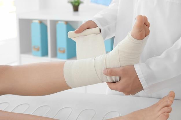 의사는 클리닉, 근접 촬영에서 환자의 다리에 붕대를 적용