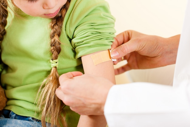 Doctor applying bandage - pediatrician