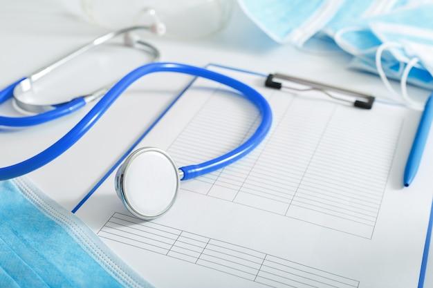 医師の任命。青い聴診器、医療テストフォームクリニックのオフィスで医師の職場のドキュメント。概念医学医療。コロノウイルスcovid-19予防