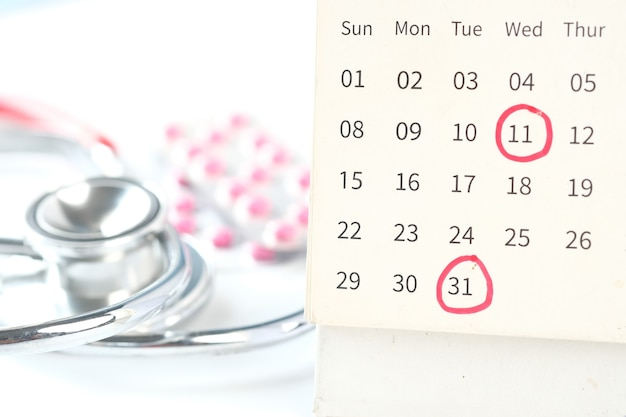Doctor appointment concept with calendar and stethoscope on white