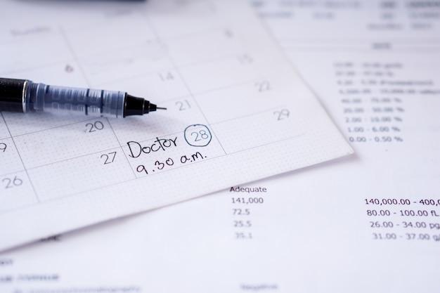 医師の予定日時を記入したカレンダーにメモをメモする
