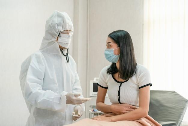 医師はアジアの女性患者の症状を尋ねるフェイスマスクを着用してベッド病院でコロナウイルスの蔓延を防ぐ