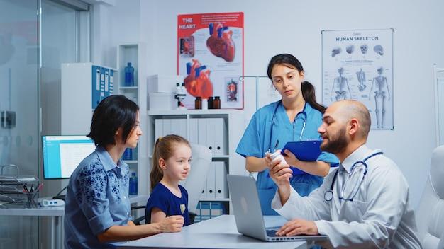 診療所での診察中に、医師が看護師に錠剤を求めている。病院内閣で医療サービス相談診断検査治療を提供する医学の医師スペシャリスト