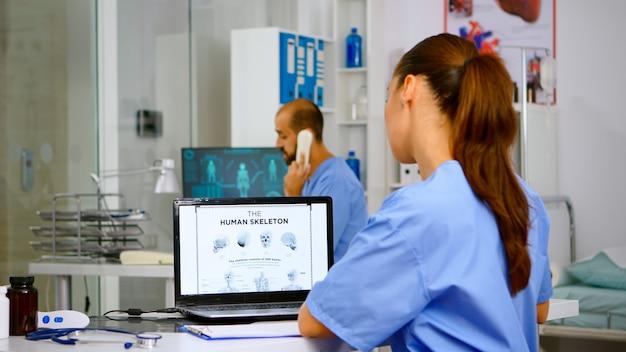 Doctor assistant analyzing digital human skeleton on laptop, taking notes on clipboard. radiologist nurse in medicine uniform looking at digital radiography, bones examination, diagnosis
