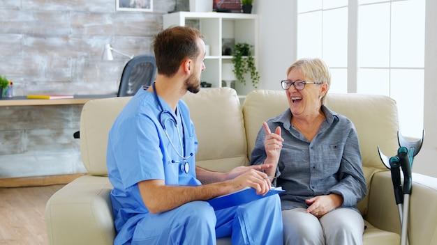 ナーシングホームで引退した老婆の話を聞きながらクリップボードにメモをとる医師助手。介護者とソーシャルワーカー