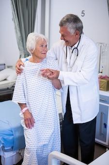 Врач, помогающий старшему пациенту в палате