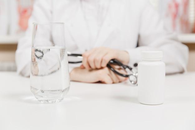 病院のオフィスでボトルの白い錠剤、コップ一杯の水を持って机の上の医者。女性は診察室で聴診器を手に持っています。医学の概念