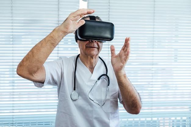 Врач у окна больницы, используя очки виртуальной реальности в медицинских целях, касаясь чего-то виртуального руками