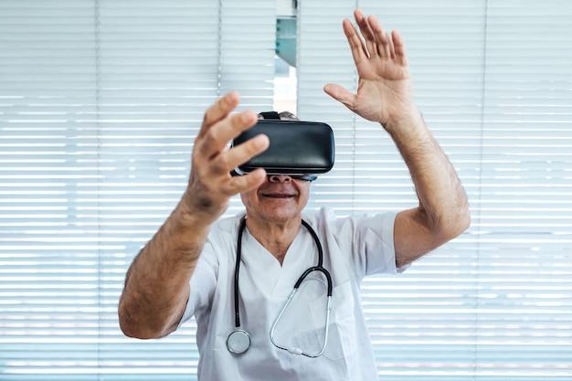 Врач у окна больницы, используя очки виртуальной реальности в медицинских целях, касаясь чего-то виртуального руками Premium Фотографии