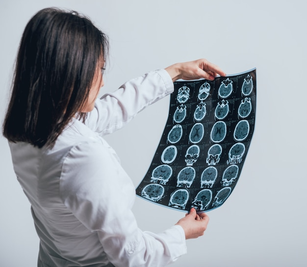 Doctor attentively examines the mri scan of the patient.
