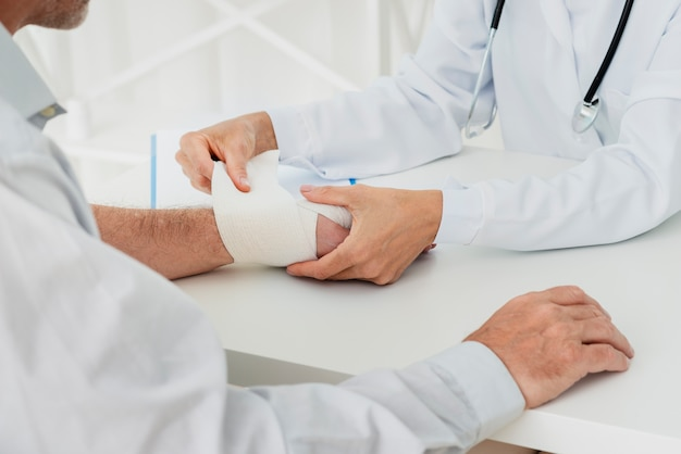 Doctor bandaging hand of patient