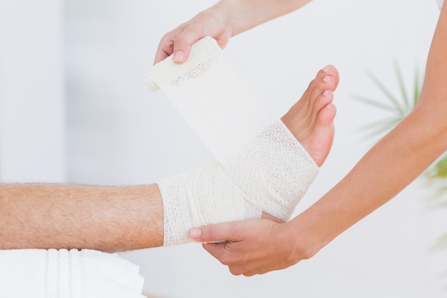 Doctor bandaging her patient ankle