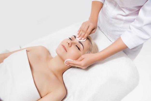 의사 미용사는 미용실에서 스폰지로 피부 여자를 정리합니다. 완벽한 청소-스파 트리트먼트 스킨 케어 얼굴. 피부 관리, 미용 및 스파 개념