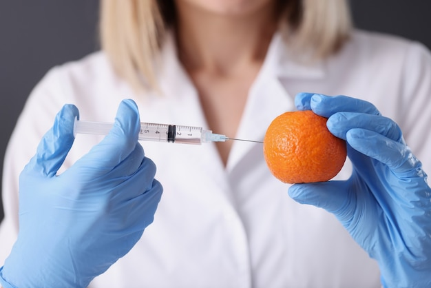 Doctor beautician in gloves making injection into orange closeup. anti aging therapy concept