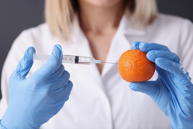 Врач косметолог в перчатках, делая инъекцию в оранжевый крупный план. концепция терапии против старения