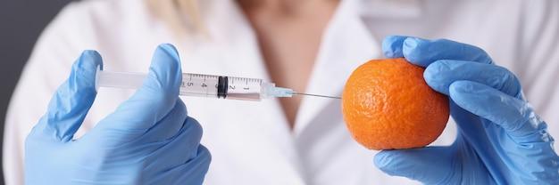 Врач косметолог в перчатках делает инъекцию в оранжевую концепцию антивозрастной терапии крупным планом