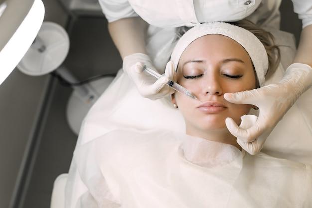 Врач-косметолог вводит лекарство в губу пациентке
