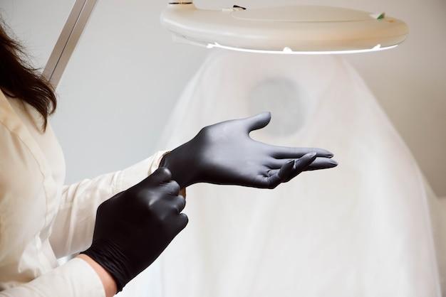 医師の美容師は、滅菌された黒い手袋を着用して、クライアントを受け入れる準備をします。