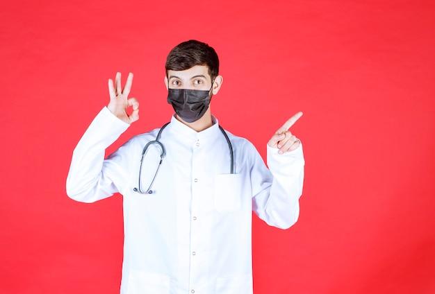 Dottore in maschera nera con stetoscopio sul collo.
