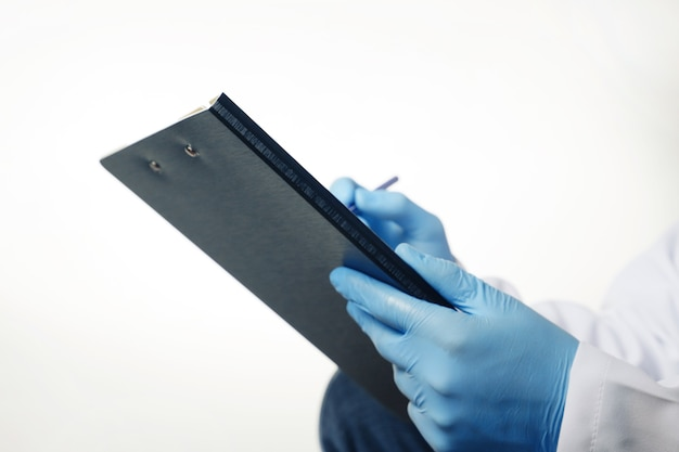 Doctor in blue gloves holding medical clipboard with empty blank sheet of paper isolated on white