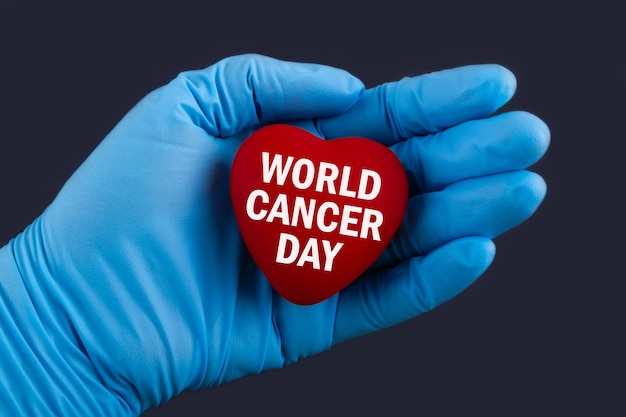 Doctor in blue gloves holds a heart with text world cancer day, concept.