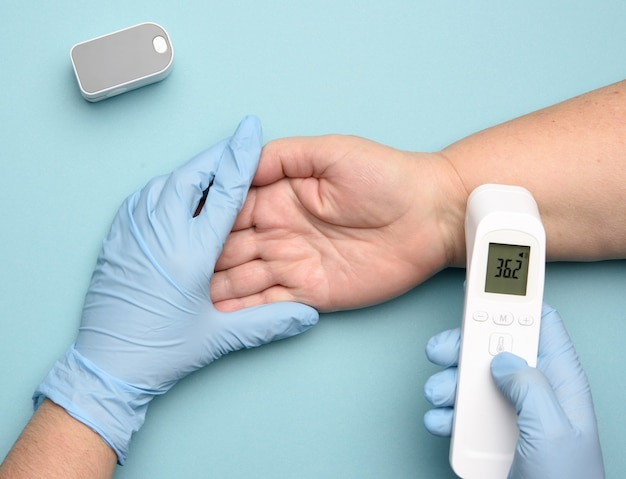 Doctor in blue latex gloves measures the temperature with an electronic contactless gadget on a woman's hand, blue background