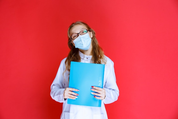 Doctor in blue mask holding the history of the patient.