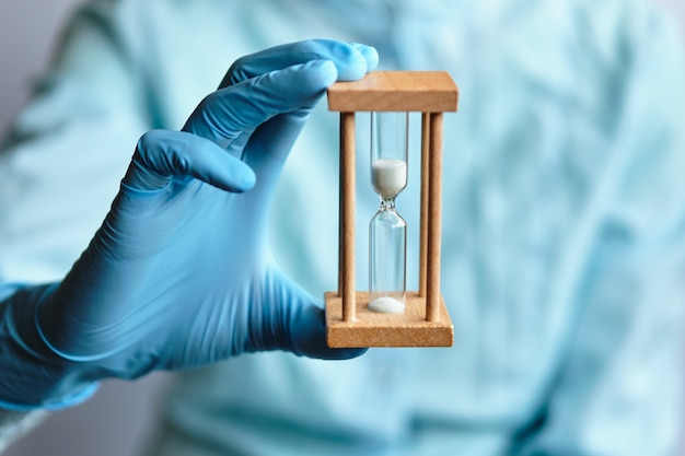 A doctor in blue medical gloves holds an hourglass - a symbol of time to heal and cure.