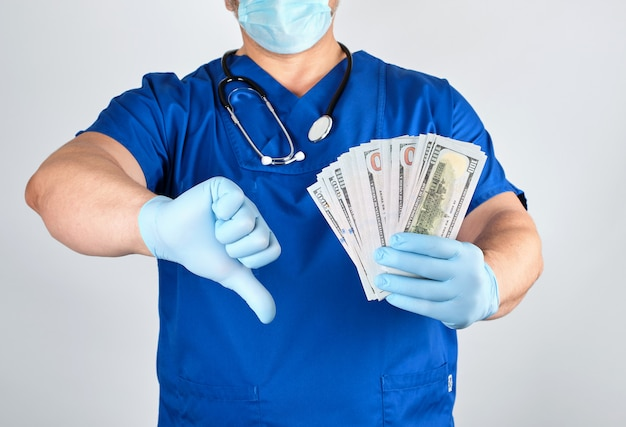 Doctor in blue uniform and latex gloves keeps one hand a lot of money, other hand shows a bad gesture