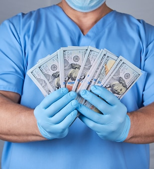 Doctor in blue uniform and latex sterile gloves holds a lot of paper money