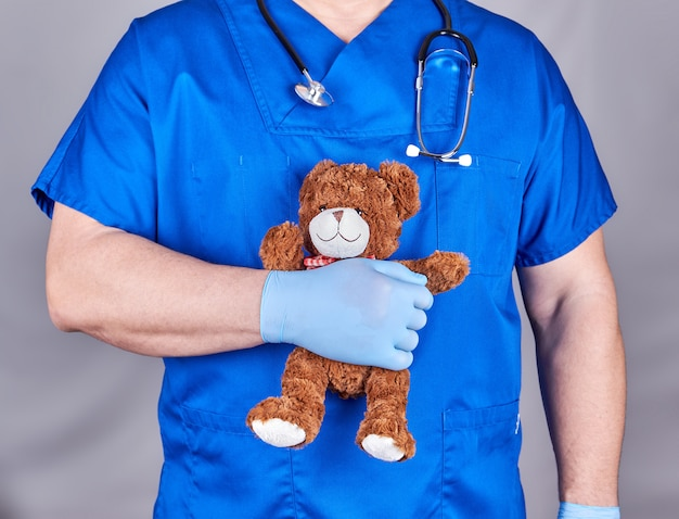 Doctor in blue uniform and old latex gloves holding a brown teddy bear