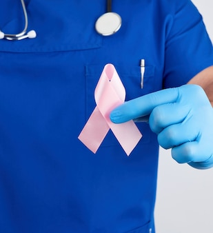 Doctor in blue uniform and sterile latex gloves holds a pink ribbon