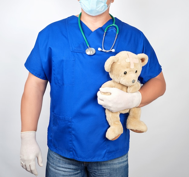 Doctor in blue uniform and white latex gloves holding a brown teddy bear