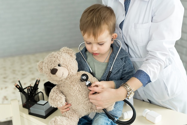 Doctor and boy patient examining teddy bear in hospital
