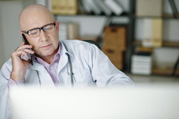 Доктор занят на мобильном телефоне