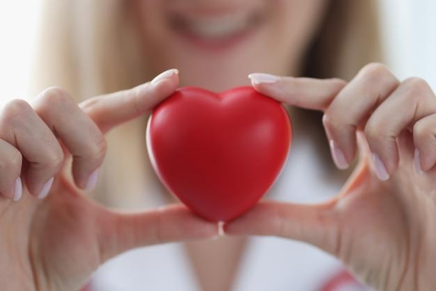 그의 손 근접 촬영에 빨간색 장난감 마음을 잡고 의사 심장. 발렌타인 데이 개념