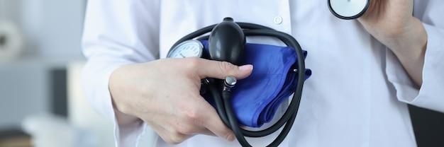 Врач кардиолог держит тонометр и стетоскоп крупным планом концепция контроля артериального давления