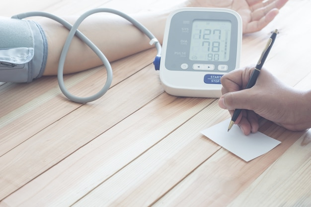 Doctor cardiologist measuring blood pressure of male patient. health concept