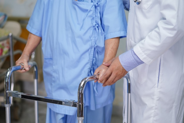 Doctor care and help senior woman patient walk with walker at hospital.