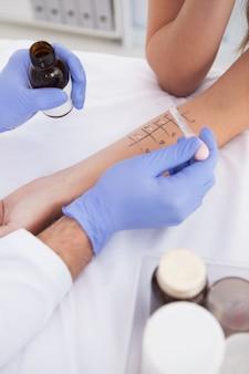 피부 찌르기 테스트를 수행하는 의사