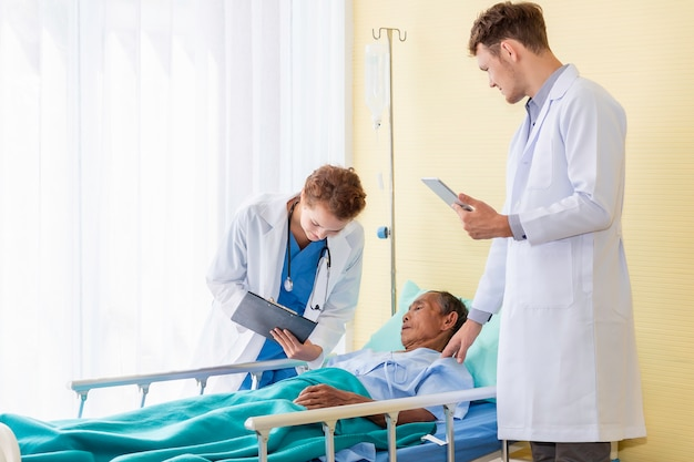 Doctor caucasian man and woman conversation and check with patient in the hospital room.