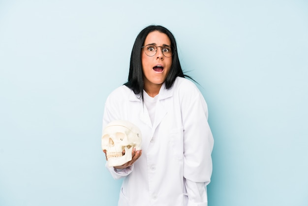 매우 화가 공격적 비명 파란색 배경에 고립 된 백인 여자 의사.