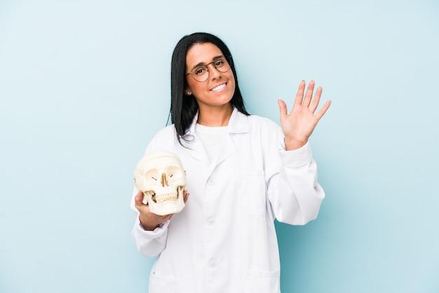 指で5番を示す陽気な笑顔の青いで隔離された白人女性医師。