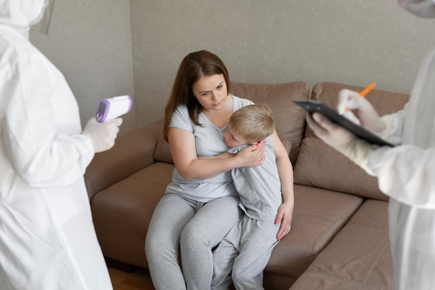 적외선 이마 온도계를 사용하여 의사가 환자 체온을 확인