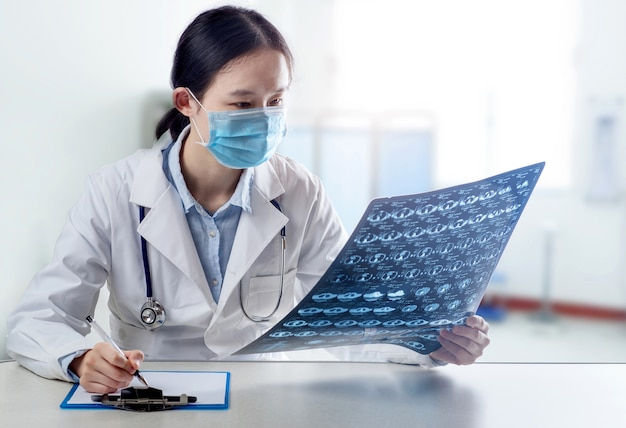 医者は病室の病院でctスキャン脳によって脳のx線フィルムをチェックします。