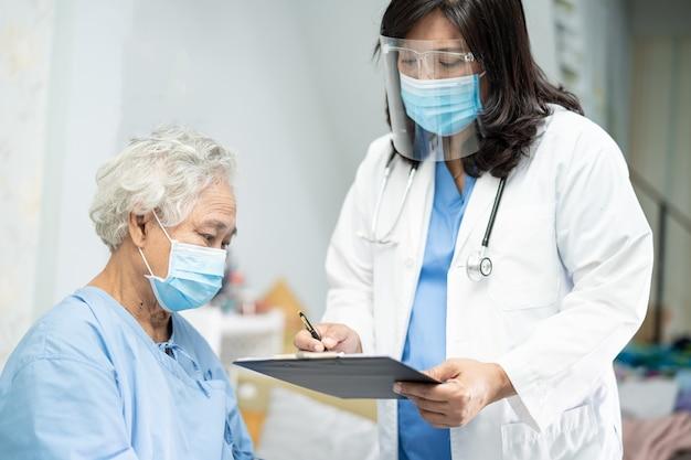 Covid-19コロナウイルスを保護するためにフェイスマスクを着用しているアジアの年配の女性患者をチェックする医師。